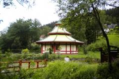 09. En oväntad kontrast i den tyska skogen. En citrongul japansk byggnad i en örtagård .