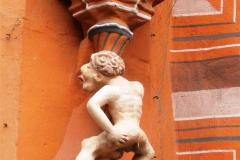19. Den mindre figuren under kvinnan är den s.k. dukatmannen. Titta noga, han fixar slantarna på sitt eget okonventionella sätt.